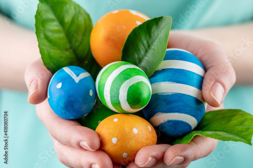 Woman is holding colorful eggs and green leaves in her hands. Concept of Easter and springtime. Closeup