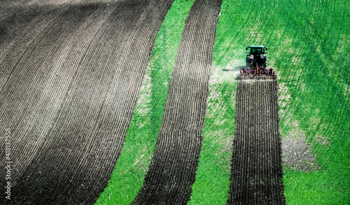 Obraz na płótnie Sunshine view of big tractor plowing the ground of green field on the slope