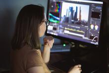Woman Video Montager Mounts Video At Desktop. Home Workstation.