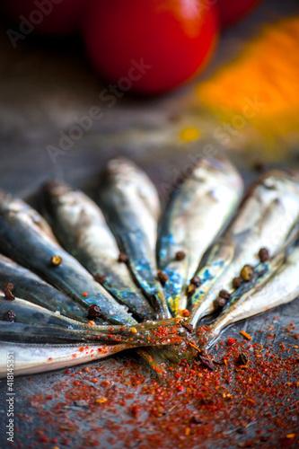 Fototapeta Small fresh sea fish lies on a dark background with bright spices obraz na płótnie
