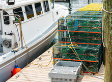 Lobster And Crab Traps Stacked On A Wod Dock Next To A Boat