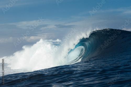 Blue wave breaking on a beach in sea