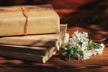 A Stack Of Old Books On A Wooden Background With A Sprig Of A Flowering Tree. The Concept Of Memorabilia