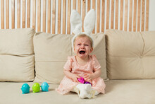 Crying Little Girl In A Headband With Bunny Ears With Egg Toys Sits On A Beige Sofa With A Basket With A Cotton Flower