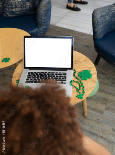 Mixed race woman celebrating st patrick's day on laptop video call with copy space on screen