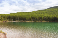 Stanton Lake Montana With Forest And Cloudy Sky Background