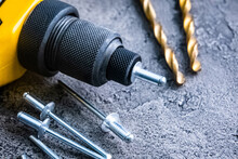 Riveter With Rivets And Drill Bits On A Table