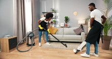 Busy African American Young Employees Vacuuming Floor With Professional Vacuum In Living Room, Cleaning Service, Small Business Concept, Working In Apron, Clean House, Professional Cleaner