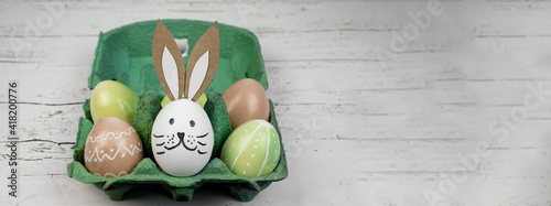 Obraz Happy Easter background banner panorama greeting card -Close-up from colorful painted eggs and easter bunny in green egg carton on rustic white vintage shabby wooden table - fototapety do salonu