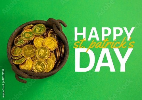 Happy st patrick's day text over bucket with gold coins on green background