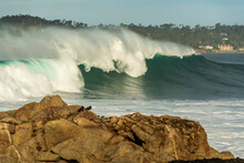 Huge Winter Waves Crashing In Carmel Bay With Pebble Beach In The Background, California.
