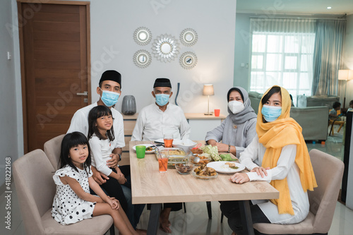 Photo portrait of happy family muslim wear mask during eid mubarak celebration at home