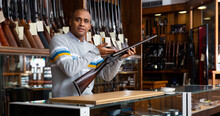 Handsome Positive Adult Male Seller In Hunting Shop With Rare Collectible Rifle In Hands