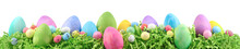 Painted Easter Eggs And Decorations On Arranged On Easter Grass. Horizontal Banner Isolated On White.