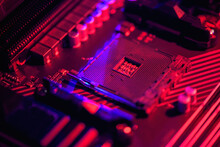 Blurred Background. Socket Am4. Close Up Of The AM4 Socket For The Motherboard With Neon Blue And Red Lights. Technological Background