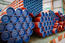 Red Steel Pipes For Fire Fighting System And Extinguishing Water Lines In Industrial Building. Paint Shop. Steel Pipe Of Round Industrial Steel Pipes Bunch On A Construction Site