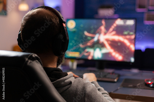Cuadros en Lienzo Back view shot of concentrate gamer streaming online videogames on computer using wireless controller