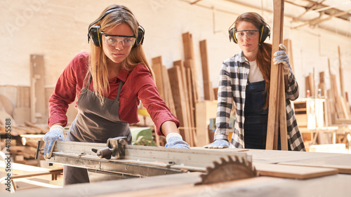 Obraz Women as carpenter apprentices at the circular saw - fototapety do salonu