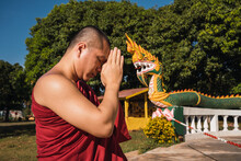 A Monk Is Worshipping And Meditating In Front Of The Golden Buddha As Part Of Buddhist Activities. Buddhist Temple In Misiones, Argentina.