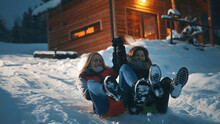Two Girls Sliding On The Sleds On Snowy Winter Evening. Winter Season, Christmas Holidays. High Quality Photo