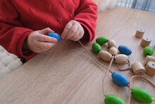 Small Child, Toddler Stringing Colored Wooden Beads On A String, Children's Fingers Close-up, Concept Of Development Of Fine Motor Skills, Tactile Sensations, Creativity, Children's Entertainment