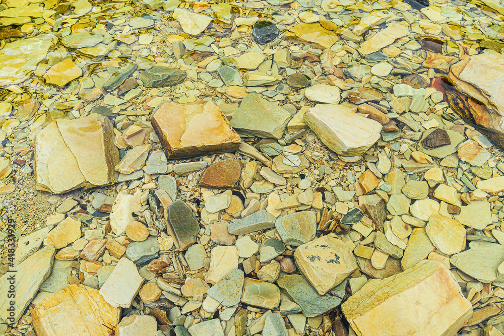 Fototapeta Underwater sedimentary rocks. Rocks in different shapes submerged on a transparent water with green tones.