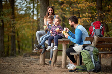 Family With Children Having Fruit Snack On Outing