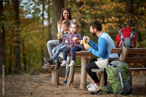 Family with children having fruit snack on outing Fototapeta