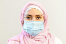 Pandemic Lifestyle Concepts. Close-up Portrait Of Islamic Woman Wearing Face Mask And Hijab During Coronavirus Epidemic, Muslim Businesswoman Protects Itself From Viruses, Isolated On White