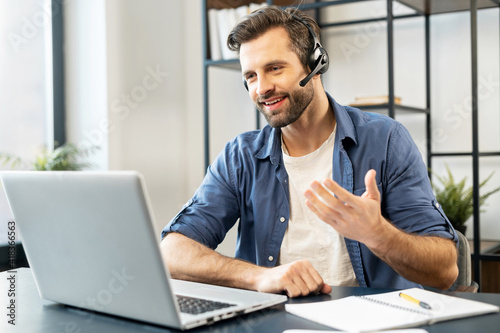 Obraz Confident man with handsome stubble, wearing headset, talking in front of computer, wearing casual clothes, talking at computer, discussing work process, gesticulates, chatting with partners, notice - fototapety do salonu