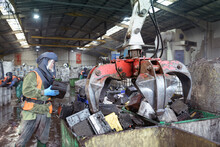 Worker In Protective Clothing Loading Vehicle Batteries Into Grab Bin In Vehicle Battery Recycling Plant