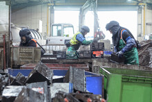 Workers In Protective Clothing Cutting Up Automotive Batteries In Vehicle Battery Recycling Plant