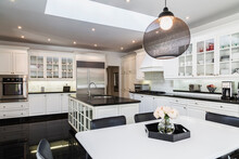 White Breakfast Table With Black Leather Chairs, White Wood And Glass Pane Island With Black Granite Countertop,  Cupboards In Country Style Kitchen, Black Granite Tile Flooring