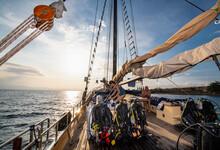 Tourists On Board Old Schooner Sailboat Navigating Waters Of Komodo Island, East Nusa Tenggara, Indonesia