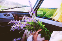 Woman Sitting In Car With Bunch Of Purple Wildflowers, Over Shoulder View
