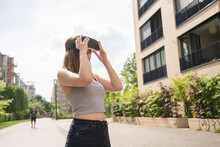 Woman Using Virtual Reality Goggles In Urban Berlin, Germany