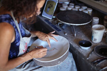 Female Potter Painting Ceramic Plate In Workshop