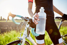 Female Cyclist Holding Water Bottle, Mid Section
