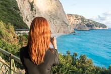 Woman Taking Photograph Of Turquoise Sea, Lefkada Island, Levkas, Greece