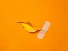 First Aid Adhesive Plaster On Torn Orange Paper
