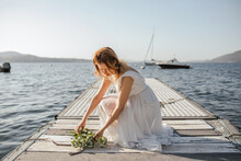 Young Bride In Wedding Dress Laying Bouquet On Lake Pier, Stresa, Piemonte, Italy