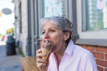 Senior Woman Sitting On Sidewalk Eating Chocolate Ice Cream Cone