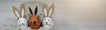 Happy Easter Background Banner Panorama Greeting Card -Close-up From White And Brown Cute Funny Painted Eggs And Easter Bunny In Egg Carton On Rustic White Vintage Shabby Wooden Table