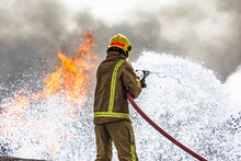 Military Airbase Fire Firefighters Tackle A Raging Blaze On An Airbase As Part Of Military Training Exercises. Towering Flames Extinguished With The Use Of Teamwork And Specialist Emergency Equipment