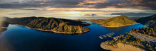 A Majestic Aerial Panoramic Shot Of The Vast Blue Still Lake Water With Breathtaking Mountain Ranges Reflecting Off The Lake At Sunset At Silverwood Lake In San Bernardino County, California