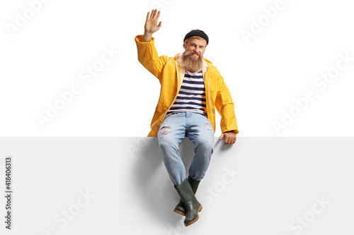 Fotografie, Obraz Bearded fisherman with a yellow rain coat sitting on a panel and waving