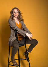 Smiling Sensual Blonde Beautiful Woman Posing In Casual Suit And  High Heels In Snakeskin Cowboy Style On A Yellow Background. Flowing Hair.