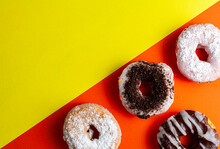 Assortment Of Decorative Sweet Fresh Baked Donuts On Two Colored Background. The Deserts With Different Finishings And Toppings Are On Orange Side While The Yellow Part Is Left Blank For Customization