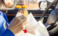 A Woman Is Eating French Fries Which She Got From A Roadside Drive Through Fast Food Chain. She Has Packs Of Food On Her Lap As She Eats In The Driver Seat Of Her Car In The Parking Lot.