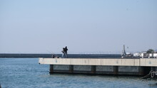 Turkey. Istanbul 04.03.2021.istanbul Kadikoy, People Fishing And Walking On Concrete Shore Bosporus Istanbul Near Haydarpasa Main Train Station During Sunny Day.